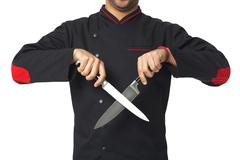 Afro American professional cook holding knifes - isolated. Stock Photos