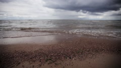 Small sea waves on beach with tiny stones. Grey cloud sky. Summer. Slider pan Stock Footage