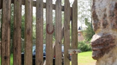 Gate with rusty horseshoe. Green courtyard, car background. Countryside. Nobody Stock Footage