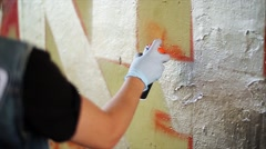 Stock Video Footage of Back side graffiti artist paint spraying the wall. Summer day. Vandalism