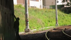 Silhouette of graffiti artist spraying the wall, walk forward. Railway on right Stock Footage