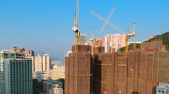 Construction cranes work on tall real estate buildings in Hong Kong Stock Footage