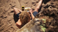 Boy sit on sand beach and eat fast food from container. Summer day. Slow motion Stock Footage