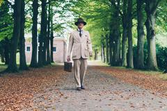 Stock Photo of Senior man with hat and suit holding suitcase. Walking in avenue.