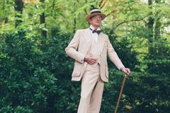 Wealthy senior man in suit standing with cane in garden. - stock photo