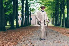 Smiling wealthy senior retro dandy in suit standing with cane in avenue. Stock Photos