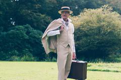Vintage commercial traveler back on his estate standing in garden. - stock photo