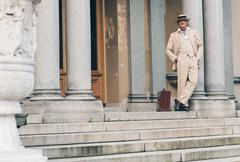 Retro commercial traveler waiting on stairs leaning against column. Stock Photos
