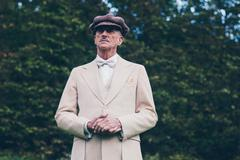 Well dressed gentleman in front of hedge. - stock photo