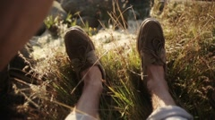 Man's feet lie and moves on green grass in summer sunny day. Counrtyside - stock footage