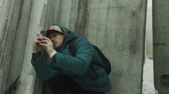 Man on a smartphone photographs and explains among concrete slabs Stock Footage