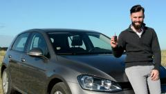 Young happy proud man show key from his new car - flaunt - he is in countryside Stock Footage