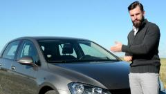 Young handsome happy smart man offer car and talk about it in the countryside  Stock Footage
