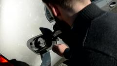 Handsome beard man checks the fuel tank in car - closeup over shoulder Stock Footage