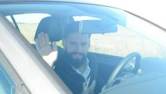 Young handsome hipster man sits in the car and waves with one hand (welcome)  Stock Footage
