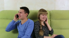 Young man and woman sitting on couch and talking on the smartphone. Lack of Stock Footage