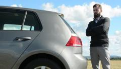Young handsome hipster man stands beside the car and looks around - countryside Stock Footage