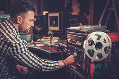 Sound engineer working with professional audio equipment in the boutique reco Stock Photos