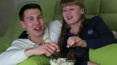 Young couple with popcorn watching comedy on television and laugh - stock footage