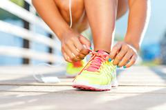 Running shoes - woman tying shoe laces - stock photo