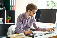 Artist drawing something on graphic tablet at the home office Stock Photos