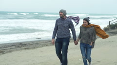Happy couple walking on the beach on a stormy day Stock Footage