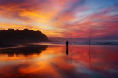 fisherman silhouette on beach at sunset - stock photo