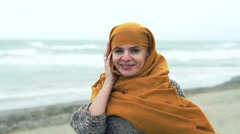 Portrait of young, pretty woman with kerchief standing on the the beach on a sto - stock footage