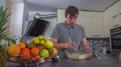A man with a grey T-shirt is making something for his breakfast Stock Footage