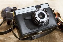 Vintage photo camera and blank film strip - stock photo