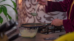 Taking one big scoop of crepe batter and putting it on a frying pan Stock Footage