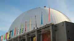 Stockholm Globe Arena - Ericsson Globe with flags in breeze Stock Footage