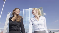 4K Beautiful businesswomen chatting as they walk through urban outdoor area Stock Footage
