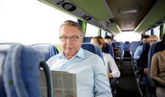 Happy senior man reading newspaper in travel bus Stock Photos