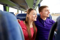 Happy teenage couple or passengers in travel bus Stock Photos