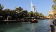 Water taxi boat sail at channel in Madinat Jumeirah, dense palm trees on shore Stock Footage
