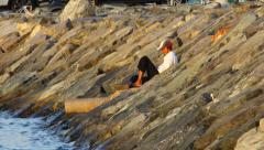Scraggy fisherman sit on stony slope, red white cat walk down and return Stock Footage