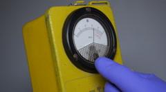 Hand holding geiger counter radioactiviy monitor Stock Footage
