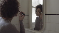 Afro American Woman in bathroom doing make-up in mirror - stock footage
