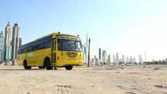 Yellow school bus parked at deserted land, modern tall skyscrapers on background Stock Footage