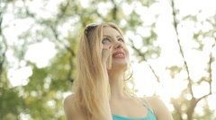Beautiful young blond woman talking on the phone outdoors in the summer - stock footage