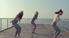 Young girls dancing modern dance on the pier near sea Stock Footage