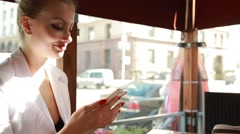 Stylish young business woman in white suit at cafe on a terrace drinking coffee - stock footage