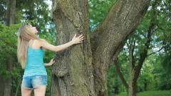 Beautiful sexy girl, long-haired blonde with long sexy legstouches huge old tree - stock footage