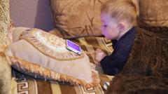 Little boy watching cartoon at a smartphone Stock Footage