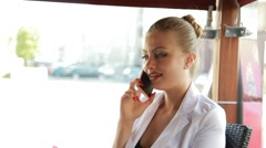 Stylish business woman in a cafe on the outdoor terrace on the phone - stock footage