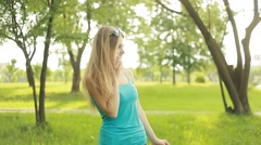 Beautiful young blond woman talking on the phone outdoors in the summer Stock Footage