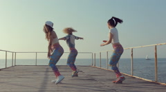 Sporty girls shaking their butts on the pier near sea Stock Footage