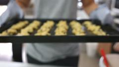 Asian woman holding cookies tray, Zoom in shot Stock Footage