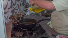 Putting sunflower oil into a frying pan Stock Footage